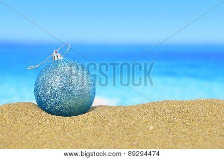 Christmas ball on sandy beach