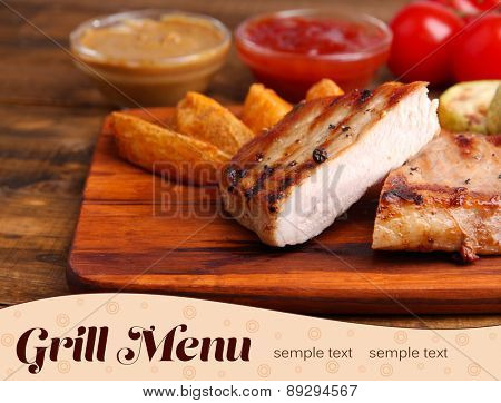 Grilled steak, vegetables and fried potato pieces on wooden board on table background