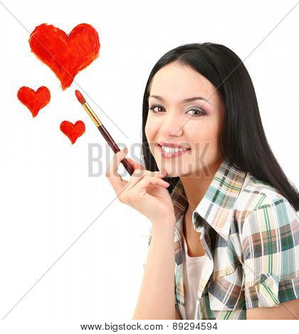 Beautiful young woman as painter with brush and red hearts isolated on white