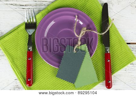 Blank tag on color plate and napkin on wooden table, top view