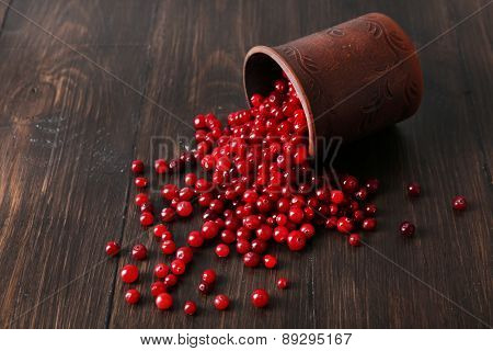 Red cranberries with cup on wooden background