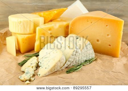 Various types of cheese with rosemary on table close up