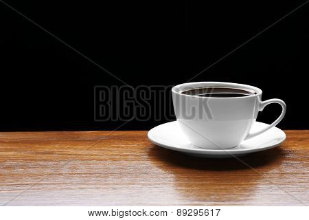 Cup of coffee on wooden table on black background