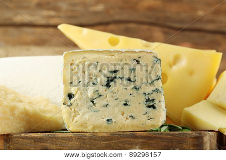 Different sort of cheese on wooden table, closeup
