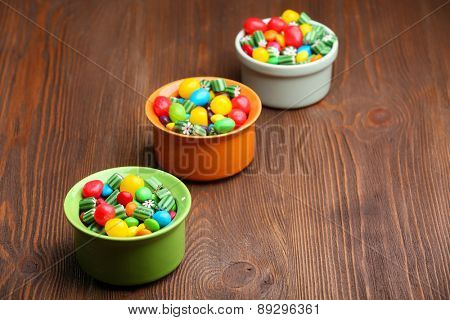 Colorful candies in bowls on wooden background