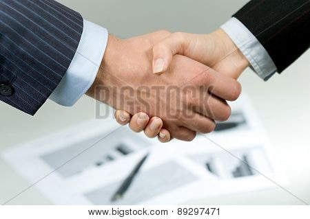 young man and woman shaking hands in a business meeting