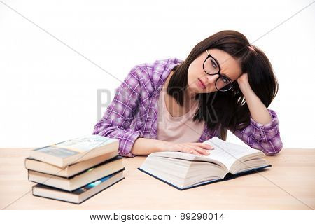Tired female student sitting at the table over white background and looking at camera