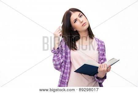 Pensive young female student standing with book over white background and looking at camera