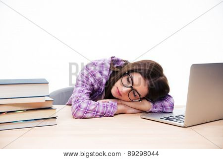Young woman in glasses sleeping on the table over white background