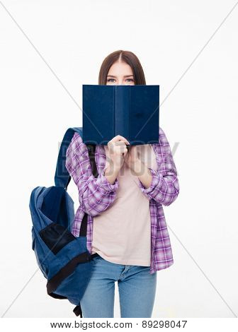 Young female student covering face with book over white background and looking at camera