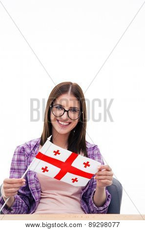 Smiling woman sitting at the table and holding Georgians flag over white background and looking at camera