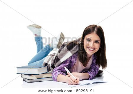 Happy woman lying on the floor and writing in notebook over white background and looking at camera