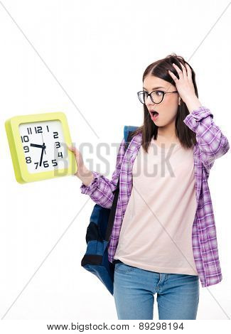 Surprised young female student looking on big clock over white background