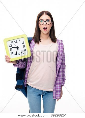 Surprised young female student holding big clock and looking at camera over white background