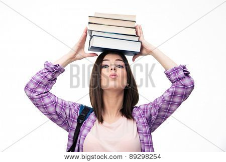 Young wowan holding books on head over white background and looking at camera