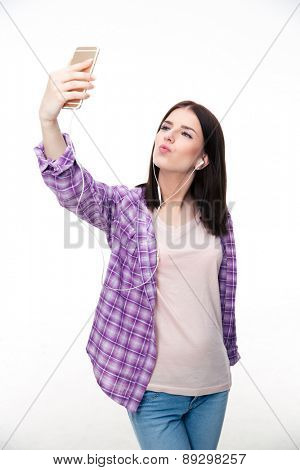 Young woman in headphones making selfie photo on smartphone over white background