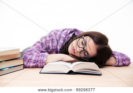 Young female student sleeping on the table with books over wihte background