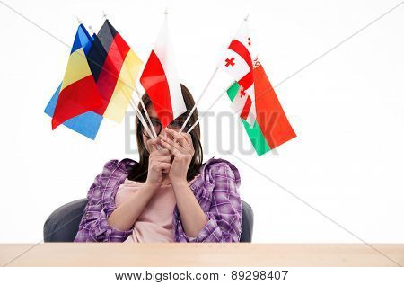 Young woman sitting at the table with international flags and looking at camera