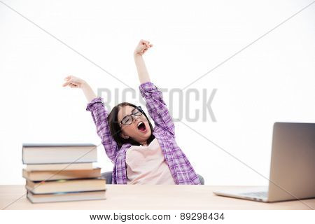 Young woman in glasses sitting at the table and yawning over white background