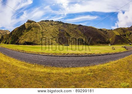 The photo was taken Fisheye lens.  On canyon there is dirt road. Camping in the canyon Pakgil, Iceland. The canyon -  green grass and moss on fantastic rocks