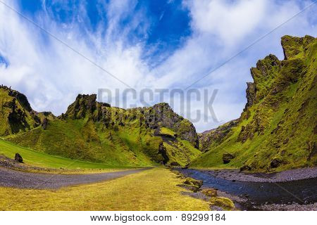 The canyon Pakgil is located among fantastic rocks. On bottom of canyon  fast shallow stream flows. Summer blossoming Iceland.The photo was taken Fisheye lens