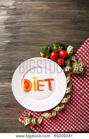 Word DIET made of sliced vegetables in white plate on wooden table, top view