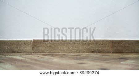 Brown Baseboard Under A White Wall