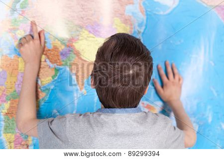 Serious Child Studying Map Of World