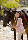 picture of horse girl  - sweet beautiful young girl 7 or 8 years old holding bridle of little pony horse smiling happy wearing safety jockey helmet posing outdoors on countryside in summer holiday - JPG