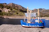 picture of figurines  - Blue Fishing Boat Figurine near the Water - JPG