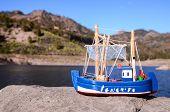 stock photo of figurines  - Blue Fishing Boat Figurine near the Water - JPG