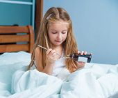 pic of cough syrup  - little girl with influenza in bed - JPG