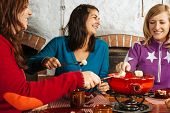 stock photo of dipping  - Photo of three beautiful females dipping bread into the melted cheese in a fondue pot - JPG