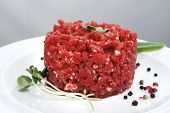 image of hamburger-steak  - very big raw hamburger cutlet with sprouts and chilli pepper on white plate over black background - JPG