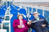 image of passenger ship  - Happy Senior Couple Relaxing On The Deck of a Luxury Passenger Cruise Ship - JPG