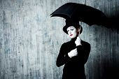 stock photo of loneliness  - Portrait of a male mime artist standing under umbrella expressing sadness and loneliness - JPG