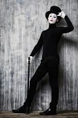 image of mime  - Full length portrait of an elegant male mime artist standing with walking stick by a grunge wall - JPG