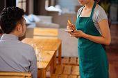 image of waiter  - Waiter taking order from her customer in a restaurant - JPG