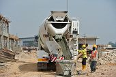 Постер, плакат: Group of construction workers pouring concrete from concrete mixer