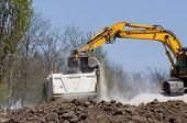 foto of heavy equipment operator  - Excavator loading truck with gravel and dirt on the road construction site - JPG
