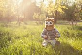 stock photo of knitwear  - Cute baby in knitwears playing at the garden - JPG