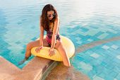 picture of mattress  - Young pretty woman with perfect tanned body lying on yellow air mattress in the pool in summer and having fun - JPG