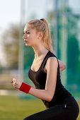 picture of track field  - Young woman running at a track and field stadium - JPG