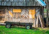 stock photo of wooden horse  - Vintage wooden cart horse carriage in the yard near the old wooden house - JPG