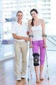 image of crutch  - Doctor helping woman walking with crutches in medical office - JPG