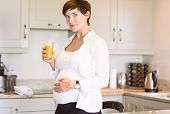 picture of orange-juice  - Pregnant woman having a glass of orange juice at home in the kitchen - JPG