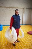 pic of convection  - group of workera installing underfloor heating and colling in modern home - JPG
