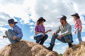 stock photo of haystack  - cowboy family of four sitting on haystacks - JPG