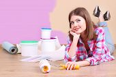 picture of wall painting  - Beautiful girl lying on floor with equipment for painting wall - JPG
