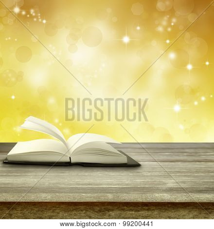 Open book on table in front of magical background